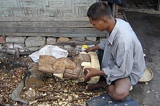 Carving a wooden Buddha statue