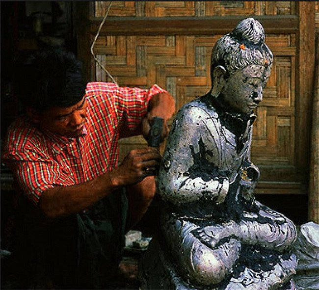Removing the mall-remains from the bronze Buddha statue