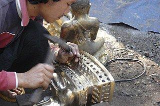 Het nabewerken van een bronzen Boeddhabeeld