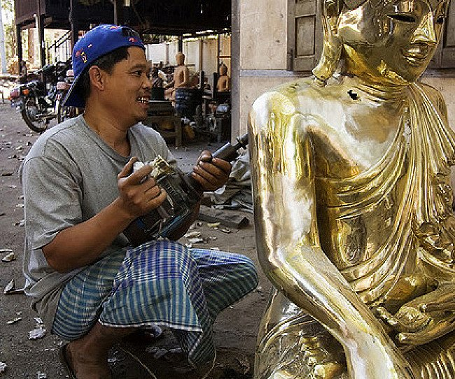 Het polijsten van een bronzen Boeddhabeeld