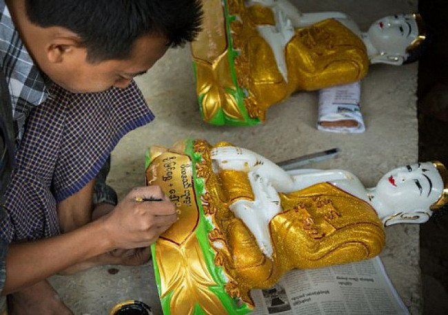 Painting a marble Buddha statue