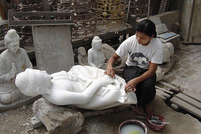 Een Birmese vrouw polijst een Boeddha