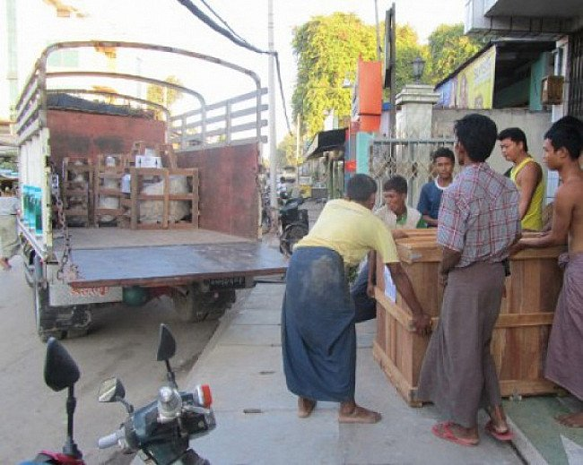Loading a crate of Buddha statues into a truck
