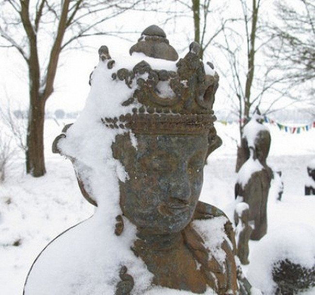 Antique Buddha statue under snow