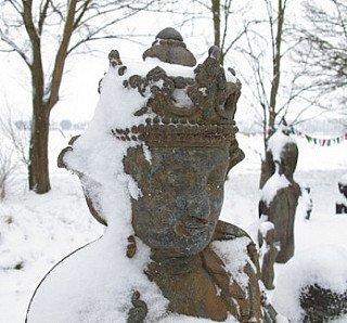 Antiek Boeddhabeeld onder de sneeuw