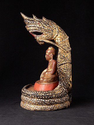 Antique wooden Buddha on Naga snake