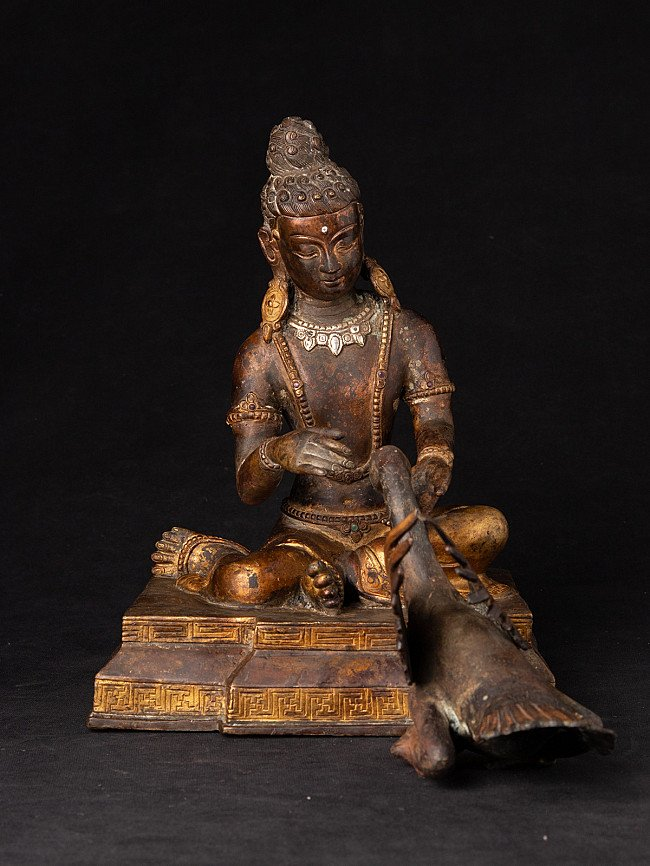 Old bronze Siddhartha with goose