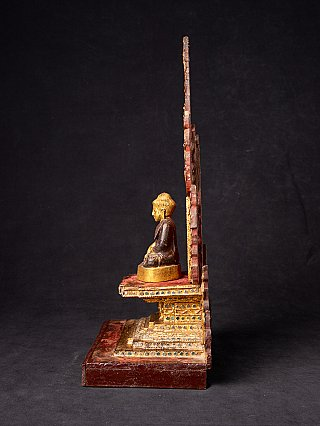 Antique wooden throne with Buddha statue