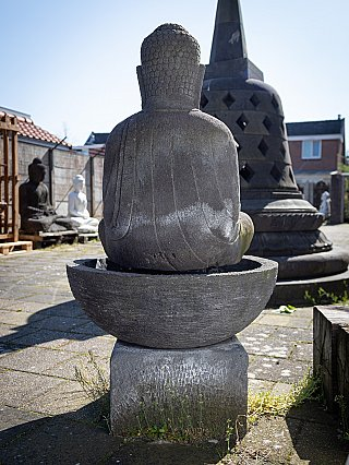 Old lavastone Buddha with waterfountain