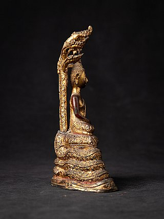 Antique bronze Thai Buddha statue on Naga snake