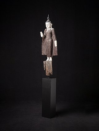 Old wooden standing Buddha statue