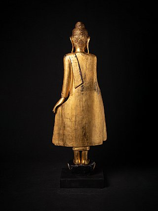 Antique wooden standing Buddha statue