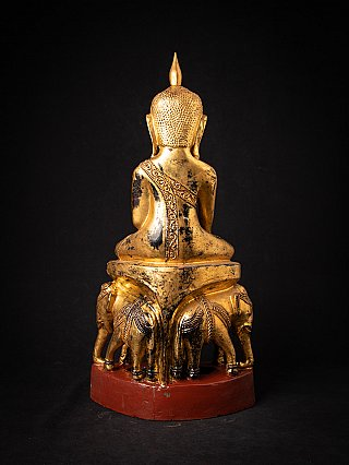 Antique wooden Buddha statue on elephant throne