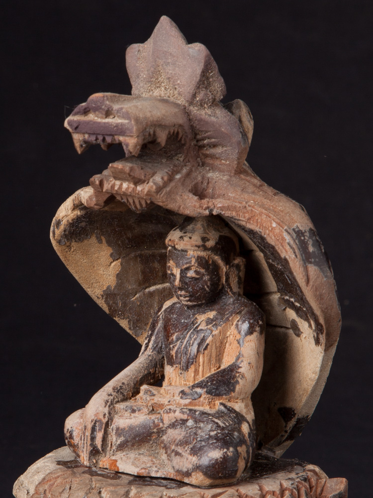 Old wooden Buddha on Naga snake from Burma made from Wood