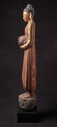 Antique wooden Buddha with offering bowl