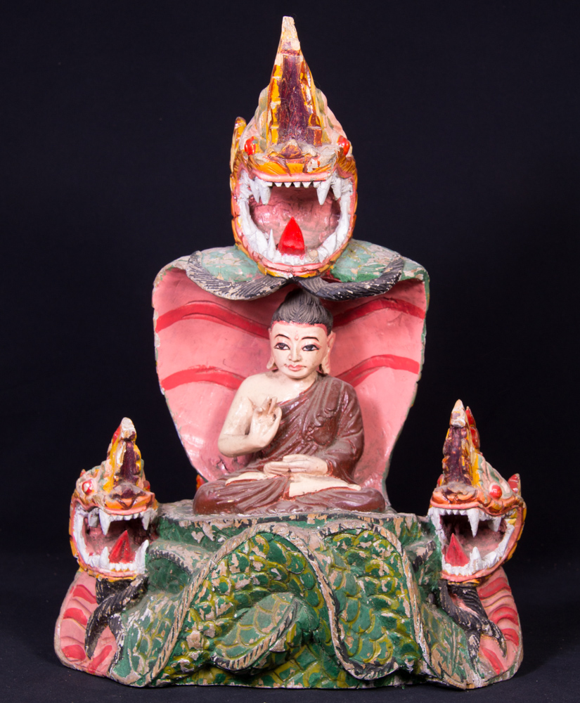 Old Burmese Buddha statue on Naga snake from Burma made from Wood