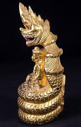 Antique wooden Buddha statue on Naga snake