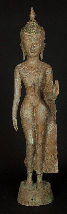 Old bronze standing Buddha statue