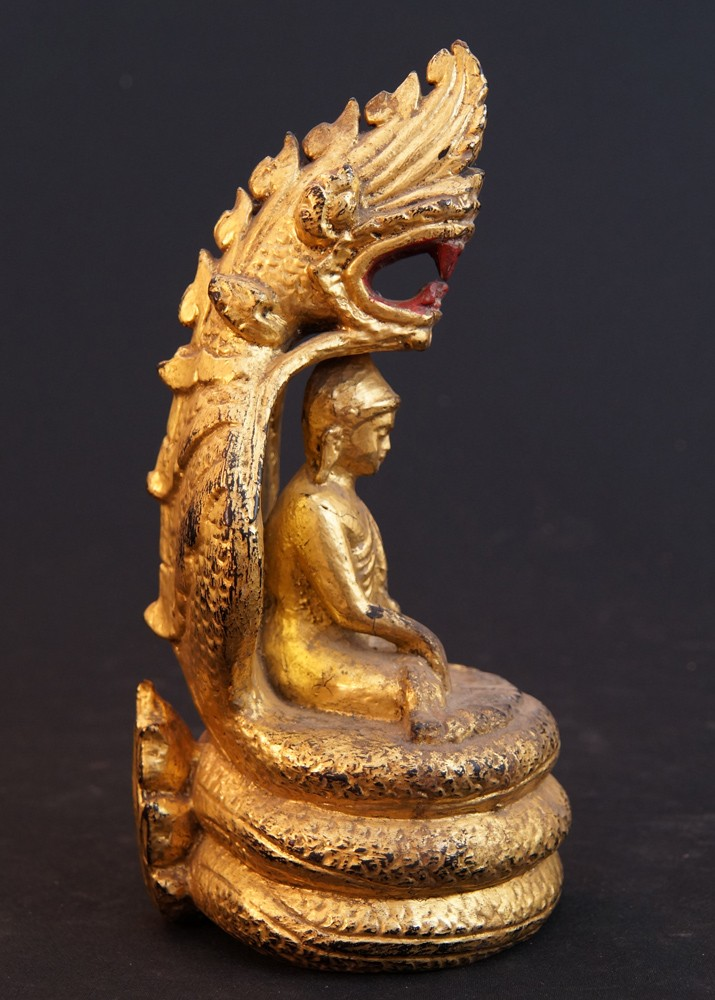 antique buddha on naga snake from burma made from wood